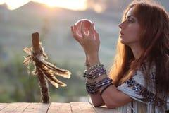 Hexe mit Glaskugel bei Sonnenuntergang Stockfotografie