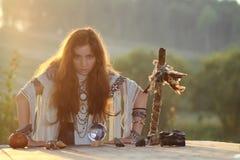 Hexe mit Glaskugel bei Sonnenuntergang Stockfoto
