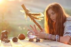 Hexe mit Glaskugel bei Sonnenuntergang Lizenzfreie Stockfotos