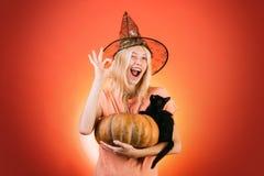 Hexe mit Kürbis und schwarzer Katze Kostüme und Hexenhüte Anzeigen-Halloween-Konzept mit lokalisierten Mädchenaufklebern stockbilder