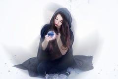 Hexe oder Frau, die Magie im schwarzen Mantel mit Glaskugel im weißen Schneewald tun Stockfotografie