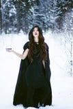 Hexe oder Frau im schwarzen Mantel mit Glaskugel im weißen Schneewald stockfoto
