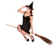 Hexefliege der jungen Frau auf Besen. Stockbilder