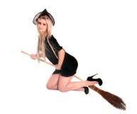 Hexefliege der jungen Frau auf Besen. Stockfoto