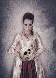 Hexenfrau im mittelalterlichen Kleid, das menschlichen Schädel in den Händen hält Stockfotografie