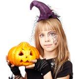 Hexenhalloween-Kostüm des kleinen Mädchens tragendes, das Kürbisisolator hält lizenzfreies stockbild