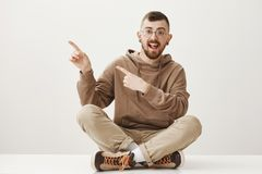Hey, check this copy space. Pleased handsome male student in glasses with stylish haircut sitting on floor, pointing at. Upper left corner with both index Stock Image