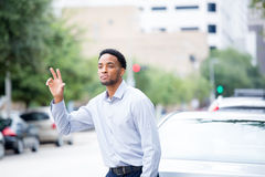 Hey. Closeup portrait, young man in blue shirt , raising hand to say hi, goodbye or hitchhike, flag or hail a cab, isolated road and cars background outdoors Royalty Free Stock Photography