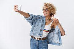 Hey followers what is up. Stylish charismatic and happy attractive young female in glasses with short curly haircut stock photography