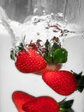 Hey fresh and cool fruites jumping in cold water. stock photos
