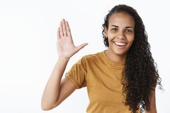 Hey high five mate. Portrait of friendly and outgoing nice attractive african american woman with long curly hair. Raising palm in hello gesture, waving to say royalty free stock photo