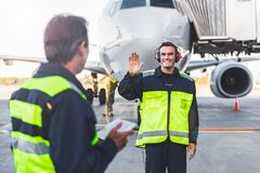 Outgoing mechanic waving hands to colleague stock photo