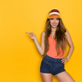 Hey! Look here. Cheerful young woman in orange shirt and sun visor pointing at copy space. Three quarter length studio shot on yellow background Stock Image