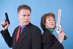 HEY! Not Fair. A man with a small automatic pistol in his hand looking confusedly at a woman with a very large revolver in her hand Royalty Free Stock Image