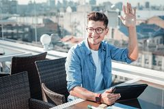 Friendly guy waving his hand while greeting somebody. Hey there. Cheerful young man working on a touchpad and smiling while seeing his friend and welcoming him Stock Photos