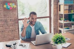 Hey there! Young cheerful afro american guy is waving in camera while having video call sitting at his work station in casual clot. Hes at home Stock Image