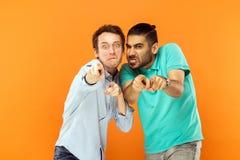 Hey voi! Due comici espressivi, facendo smorfie alla macchina fotografica Indicare aletta immagini stock libere da diritti