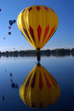 Hey wait for me!. Hot air balloon drifting over lake stock images