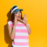 Hey You!. Excited young woman in pink stripped shirt and blue sun visor shouting and holding hands raised. Waist up studio shot on yellow background Stock Photography