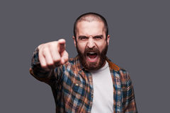 Hey you!. Furious young bearded man pointing you and shouting while standing against grey background Royalty Free Stock Photo