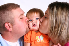 Hey You're Squishing Me 2!. A mother and father kissing their beautiful baby girl Stock Photos