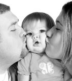 Hey You're Squishing Me 2! Black and white. A mother and father kissing their beautiful baby girl, black and white Stock Photo