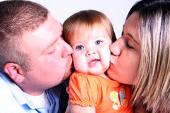 Hey You're Squishing Me!. A mother and father kissing their beautiful baby girl Stock Photo
