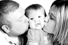 Hey You're Squishing Me! Black and white. A mother and father kissing their beautiful baby girl, black and white Royalty Free Stock Photo