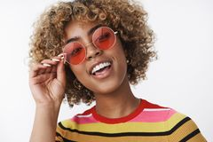 Hey you wanna have fun. Portrait of cool and stylish joyful african american party girl with blond haircut and pierced royalty free stock photo