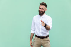 Hey you! Young adult bearded man, pointing finger and looking at camera. On light green background. Indoor. Studio shot Stock Photo
