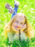 Heyday concept. Girl on smiling face spend leisure outdoors. Child enjoy spring sunny weather while lying at meadow. Girl lying on grass at grassplot, green royalty free stock photo