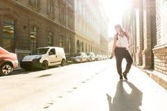 Höftflygturflicka med hörlurar i en stads- miljö Royaltyfri Bild