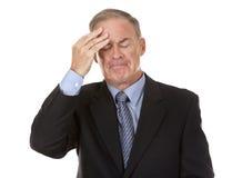 Hög affärsman som har huvudvärk Arkivbild
