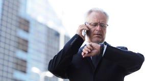 Hög affärsman som kallar på smartphonen i stad arkivfilmer