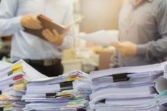 Hög av oavslutade dokument på kontorsskrivbordet Arkivbild