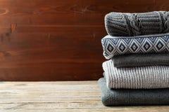 Hög av stucken vinterkläder på träbakgrund, tröjor, stickade plagg Fotografering för Bildbyråer