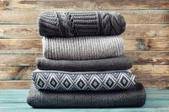 Hög av stucken vinterkläder på träbakgrund, tröjor, stickade plagg Arkivbild