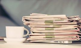 Hög av tidningar och kaffe Royaltyfria Bilder