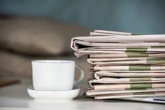 Hög av tidningar och kaffekoppen Royaltyfria Bilder