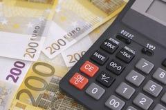 Hög av tvåhundra den eurosedlar och räknemaskinen Arkivfoto