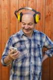 Hög byggmästare i skyddande hörlurar som rymmer händer i telefon och läs- meddelande Royaltyfria Foton