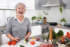 Hög eller äldre kvinna med grå hårmatlagning i kök Fotografering för Bildbyråer