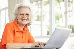 Hög kinesisk kvinna som hemma använder bärbar dator Arkivfoton