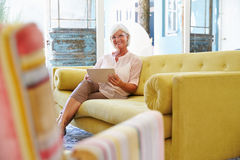 Hög kvinna hemma i vardagsrum genom att använda den Digital minnestavlan Arkivbild