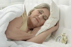 Hög kvinna i säng Arkivbilder