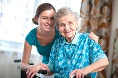 Hög kvinna med den hem- anhörigvårdaren Royaltyfri Fotografi