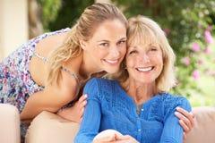 Hög kvinna med den vuxna dottern som hemma kopplar av Royaltyfria Bilder