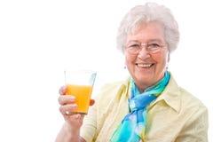 Hög kvinna med ett exponeringsglas av fruktsaft Arkivfoton
