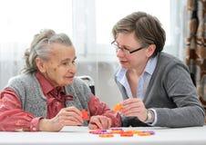 Hög kvinna med hennes äldre omsorgsjuksköterska Arkivfoto