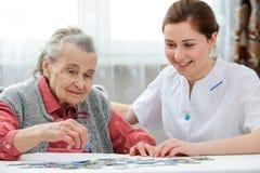Hög kvinna med hennes äldre omsorgsjuksköterska Fotografering för Bildbyråer